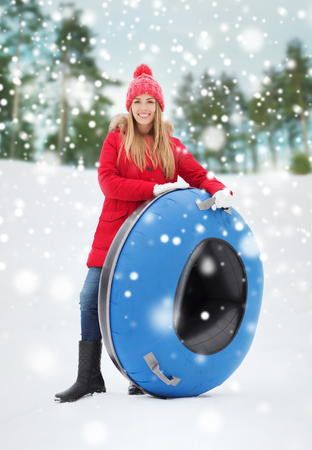 teenage girl: winter, leisure, sport, and people concept - happy teenage girl or woman with snow tube outdoors Stock Photo