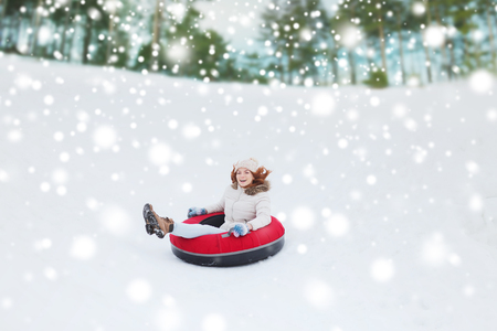 teen girls: winter, leisure, sport, and people concept - happy teenage girl or woman sliding down on snow tube