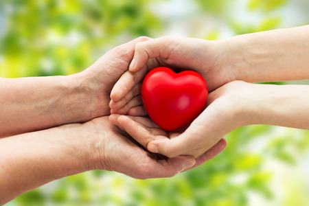 nursing aid: people, age, family, love and health care concept - close up of senior woman and young woman hands holding red heart over green natural background