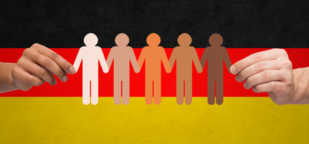 group of men: community, unity, population, race and humanity concept - multiracial couple hands holding chain of paper people pictogram over german flag background
