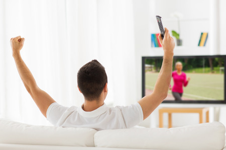 leisure, technology, mass media and people concept - man with remote control watching sport channel on tv and supporting at home from back