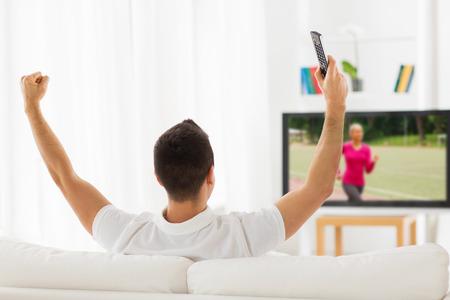 back: ocio, tecnolog�a, medios de comunicaci�n y la gente concepto - hombre con mando a distancia viendo el canal de deportes en la televisi�n y el apoyo en la casa de atr�s