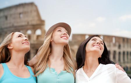 mujeres felices: vacaciones de verano, la gente, los viajes, el turismo y el concepto de vacaciones - grupo de mujeres jóvenes sonrientes sobre Coliseo de Roma fondo
