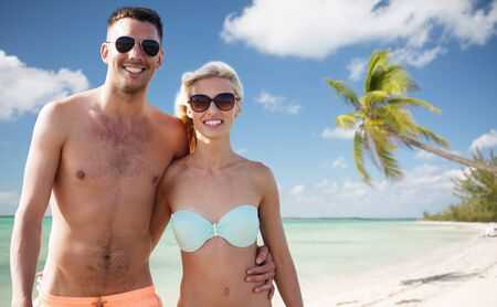 fling: love, travel, tourism, summer and people concept - smiling couple on vacation in swimwear and sunglasses hugging over tropical beach background Stock Photo
