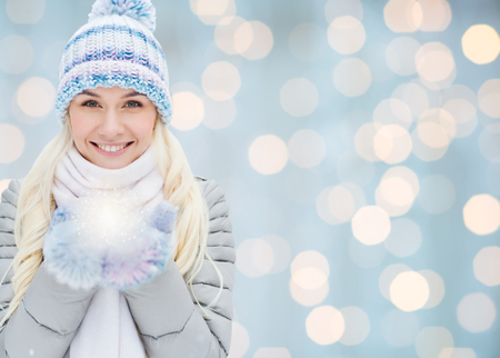 season, christmas, holidays and people concept - smiling young woman in winter clothes over lights background 스톡 콘텐츠