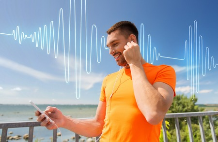 people listening: fitness, sport, people, technology and healthy lifestyle concept - smiling young man with smartphone and earphones listening to music at summer seaside over sound wave or signal diagram