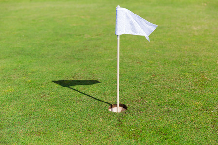play golf: game, entertainment, sport and leisure concept - close up of flag mark in hole on golf field
