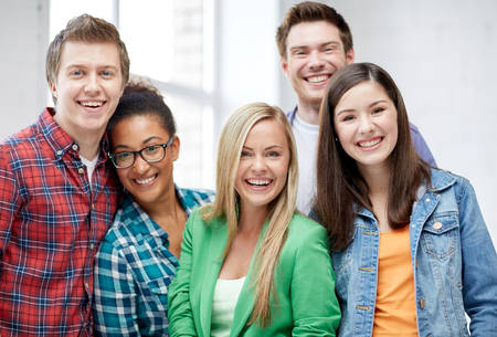 out time: education, people, friendship and learning concept - group of happy international high school students or classmates Stock Photo