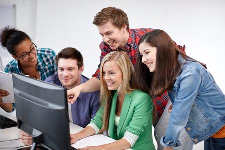 on high: la educación, la gente, la amistad, la tecnología y el concepto de aprendizaje - grupo de estudiantes de secundaria internacionales felices o compañeros de clase en clase de computación Foto de archivo