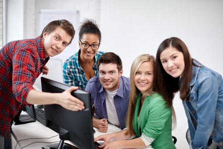 learning computer: education, people, friendship, technology and learning concept - group of happy international high school students or classmates in computer class