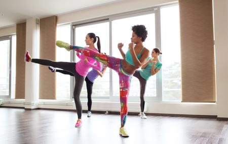 fitnes: fitness, sport, opleiding, fitness en martial arts concept - groep vrouwen uit te werken en te vechten in de sportschool