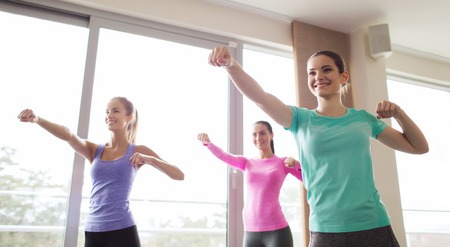 martial arts woman: fitness, sport, training, gym and martial arts concept - group of happy women working out and fighting in gym Stock Photo