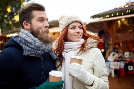 calor: días de fiesta, invierno, navidad, bebidas calientes y personas concepto - feliz pareja de turistas en ropa de abrigo que beben el café en vasos de papel desechables en el casco antiguo