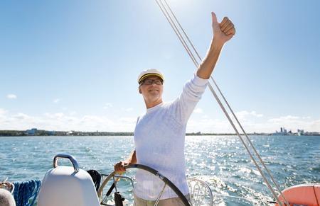 timon de barco: la vela, la edad, el turismo, los viajes y el concepto de la gente - hombre mayor feliz en el sombrero de capitán en el volante y el pulgar hacia arriba barco de vela o de yates flotan en el mar mostrando