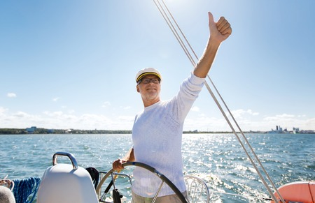 sailing: sailing, age, tourism, travel and people concept - happy senior man in captain hat on steering wheel and showing thumbs up sail boat or yacht floating in sea