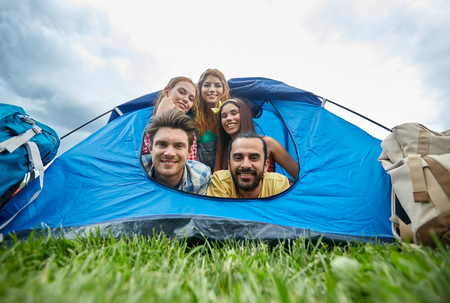 travel, tourism, hike, equipment and people concept - group of happy friends with backpacks in tent at camping