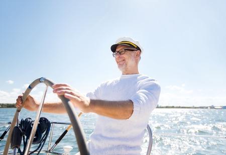 timon de barco: la vela, la edad, el turismo, los viajes y el concepto de la gente - hombre mayor feliz en el sombrero de capitán en el volante y la navegación del barco de vela o yate que flota en el mar Foto de archivo