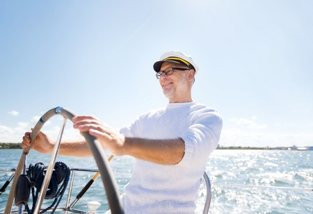 sailing ship: sailing, age, tourism, travel and people concept - happy senior man in captain hat on steering wheel and navigating sail boat or yacht floating in sea