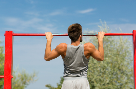 calisthenics: fitness, sport, exercising, training and lifestyle concept - young man doing pull ups on horizontal bar outdoors