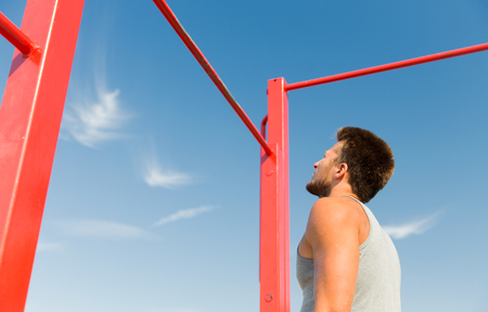 calisthenics: fitness, sport, exercising and lifestyle concept - young man standing and looking at horizontal bar outdoors