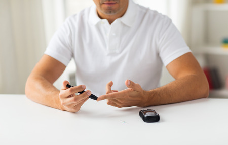 test: medicine, diabetes, glycemia, health care and people concept - close up of man checking blood sugar level by glucometer at home