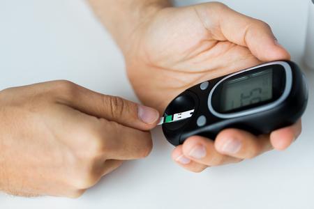 Medizin, Diabetes, Blutzucker, Gesundheitsversorgung und Personen-Konzept - Nahaufnahme von Mann die Kontrolle des Blutzuckerspiegels durch glucometer und Teststreifen zu Hause Standard-Bild