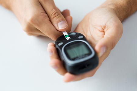 diabetes: la medicina, la diabetes, la glucemia, la salud y las personas concepto - cerca del hombre de revisar el nivel de azúcar en la sangre mediante glucómetro y raya de prueba en casa