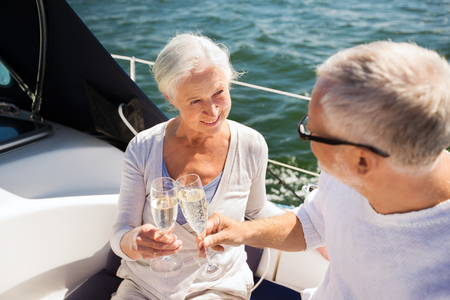 happy senior: sailing, age, travel, holidays and people concept - happy senior couple clinking champagne glasses on sail boat or yacht deck floating in sea Stock Photo