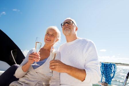 zeilen, leeftijd, reizen, vakantie en mensen concept - gelukkig senior paar met champagne glazen op een zeilboot of jacht dek drijvend in zee Stockfoto