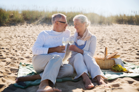 seniors: family, age, travel, tourism and people concept - happy senior couple having picnic and talking on summer beach Stock Photo