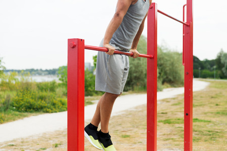 calisthenics: fitness, sport, exercising, training and lifestyle concept - close up of young man doing pull ups on horizontal bar outdoors