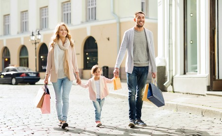 sale, consumerism and people concept - happy family with little child and shopping bags in city Foto de archivo