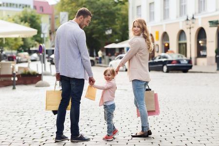 Venta, el consumismo y el concepto de la gente - la familia feliz con los niños y tiendas pequeñas bolsas en la ciudad Foto de archivo - 48220928