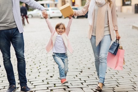 sale, consumerism and people concept - happy family with little child and shopping bags in city Stock Photo