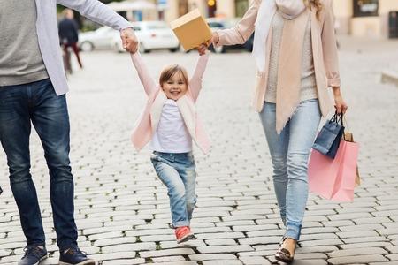 Venta, el consumismo y el concepto de la gente - la familia feliz con los niños y tiendas pequeñas bolsas en la ciudad Foto de archivo - 48220984