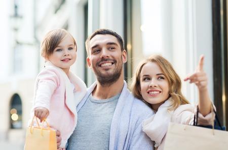 rodzina: sprzedaż, konsumpcjonizm i ludzie koncepcja - szczęśliwa rodzina z małym dzieckiem i torby na zakupy w mieście Zdjęcie Seryjne