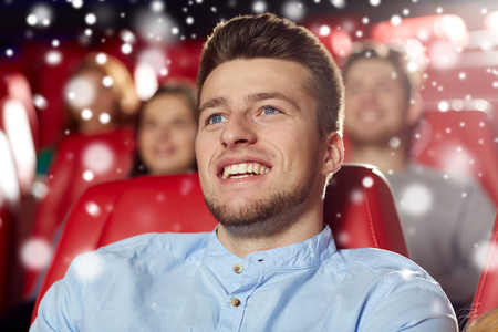 winter theater: cinema, entertainment and people concept - happy young man watching comedy movie in theater with snowflakes