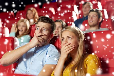 drama: cinema, entertainment and people concept - terrified friends or couple watching horror, drama or thriller movie in theater with snowflakes Stock Photo