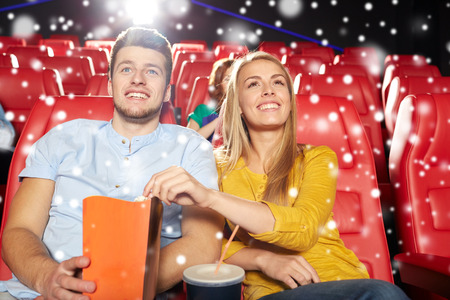 christmas movies: cinema, entertainment and people concept - happy friends or couple with popcorn and lemonade drink watching movie in theater with snowflakes