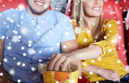 christmas movies: entertainment, leisure and people concept - close up of happy couple watching movie and eating popcorn in theater or cinema over snowflakes Stock Photo