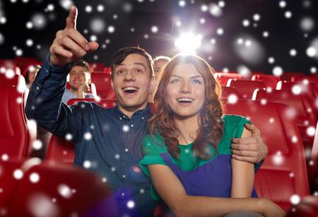 teatro: cine, entretenimiento, gestos, las emociones y la gente concepto - feliz pareja viendo la pel�cula de se�alar con el dedo a la pantalla en el teatro con copos de nieve Foto de archivo