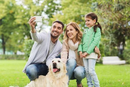 家族、ペット、動物、技術、人のコンセプト - 公園でスマート フォンで selfie を取ってラブラドル ・ レトリーバー犬犬と幸せな家庭