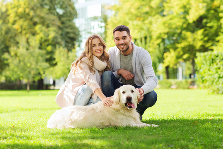 walking in park: family, pet, animal and people concept - happy couple with labrador retriever dog walking in city park
