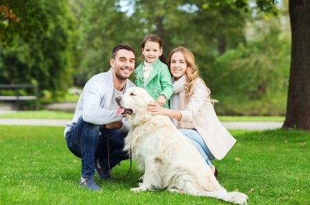 domestico: familia, mascotas, animales domésticos y las personas concepto - familia feliz con el perro labrador retriever en caminata en el parque de verano