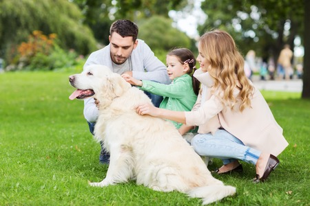 pet: family, pet, domestic animal and people concept - happy family with labrador retriever dog on walk in summer park Stock Photo