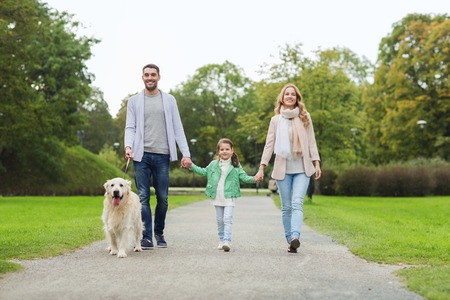 domestic animals: family, pet, domestic animal and people concept - happy family with labrador retriever dog walking  in summer park