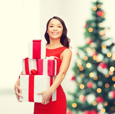 fancy box: christmas, x-mas, celebration concept - smiling woman in red dress with many gift boxes