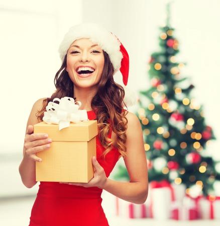 Vánoce, vánoce, nový rok, v zimě, štěstí koncept - usmívající se žena v santa pomocník klobouk s dárkové krabici