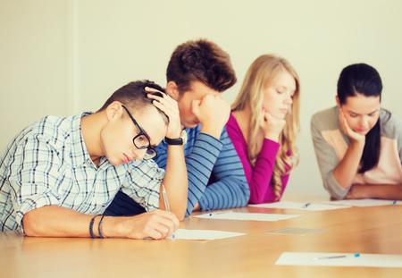 personas pensando: la educación, la escuela, la prueba y la gente concepto - grupo de estudiantes con los papeles de pensar o de hacer la prueba Foto de archivo