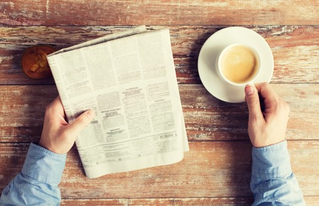 ビジネス、情報、人、マスメディアの概念 - は、テーブルの上の新聞、マフィンとコーヒーのカップを持つ男性の手のクローズ アップ